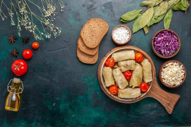 Vista superior saborosa refeição de carne enrolada com repolho e tomate chamado dolma com óleo e pão em azul escuro