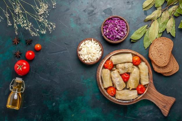 Vista superior saborosa refeição de carne enrolada com repolho e tomate chamado dolma com óleo na mesa azul escura