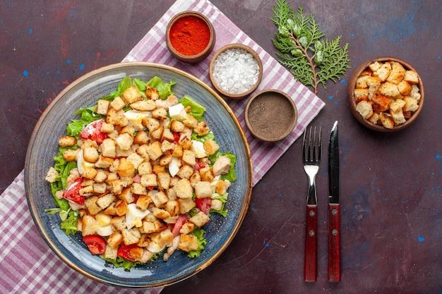 Vista superior saborosa salada caesar com bolachas e temperos na superfície escura