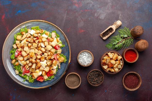 Vista superior saborosa salada caesar com temperos diferentes em mesa roxa escura
