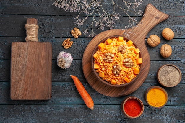 Vista superior saborosa salada de cenoura com nozes e temperos em azul escuro salada de mesa cor de nozes dieta alimentar