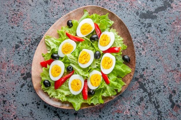 Vista superior saborosa salada de ovo com salada verde e azeitonas dentro do prato com luz de fundo