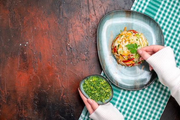 Vista superior saborosa salada de vegetais dentro do prato com as mãos femininas na mesa escura