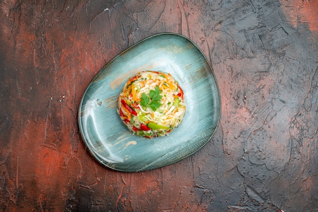 Vista superior saborosa salada de vegetais redonda em forma de prato na mesa escura