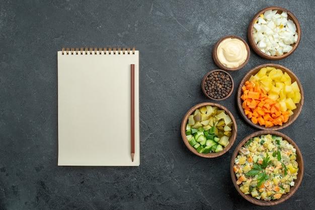 Vista superior saborosa salada mayyonaise com vegetais frescos fatiados no preto