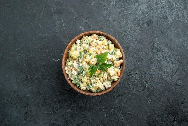 Vista superior saborosa salada mayyonaise dentro de prato marrom no preto