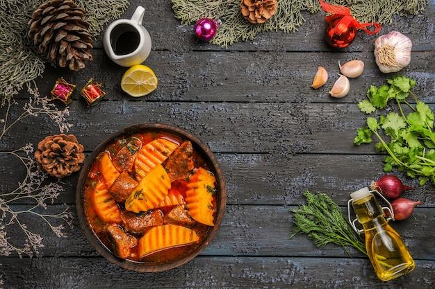 Vista superior saborosa sopa carnuda com batatas na mesa escura