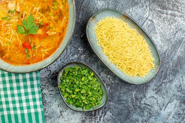 Vista superior saborosa sopa de aletria com verduras e aletria crua na mesa cinza claro