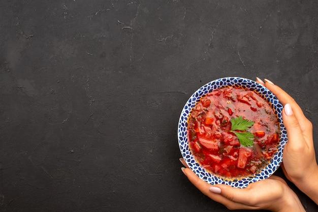 Vista superior saborosa sopa de beterraba ucraniana famosa de borsch no espaço escuro