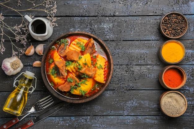 Vista superior saborosa sopa de carne com temperos em uma mesa escura