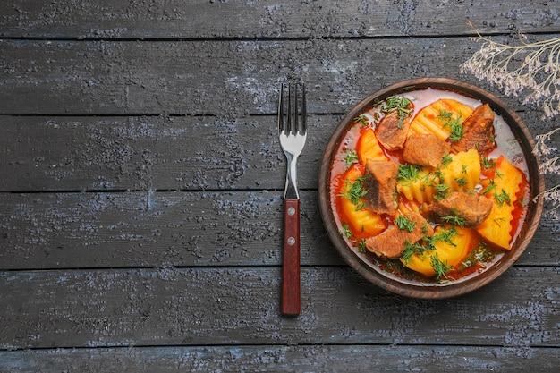 Vista superior saborosa sopa de carne com verduras e batatas na mesa escura
