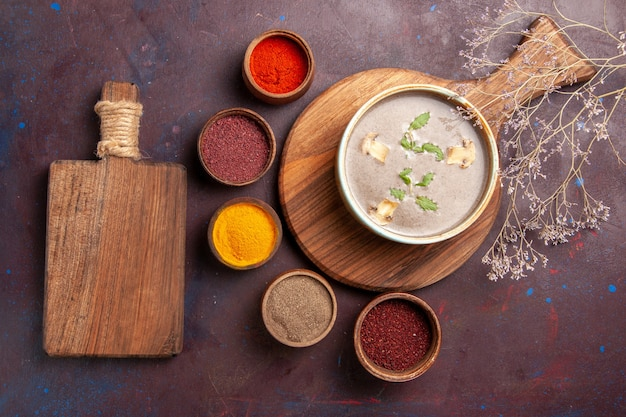 Vista superior saborosa sopa de cogumelos com diferentes temperos em fundo escuro sopa refeição de vegetais jantar comida