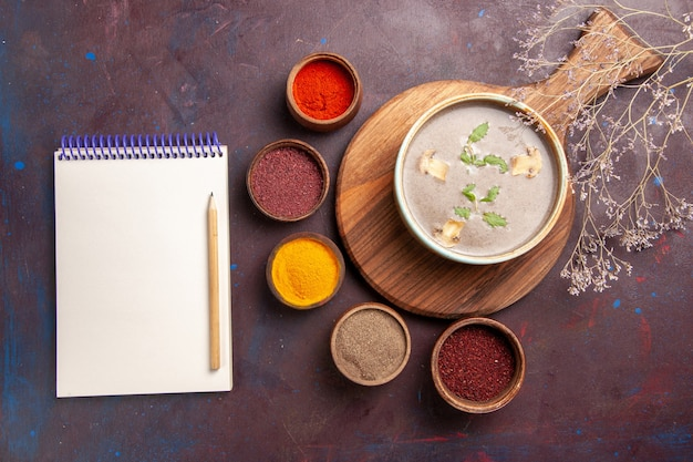 Vista superior saborosa sopa de cogumelos com diferentes temperos em fundo escuro sopa vegetais refeição comida cogumelo