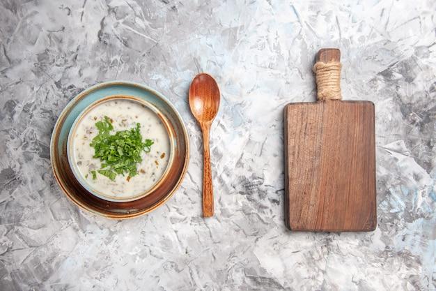 Vista superior saborosa sopa de iogurte dovga com verduras na mesa branca com leite e leite