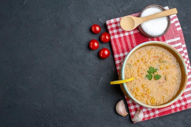 Vista superior saborosa sopa de lentilha com tomate e sal na superfície escura