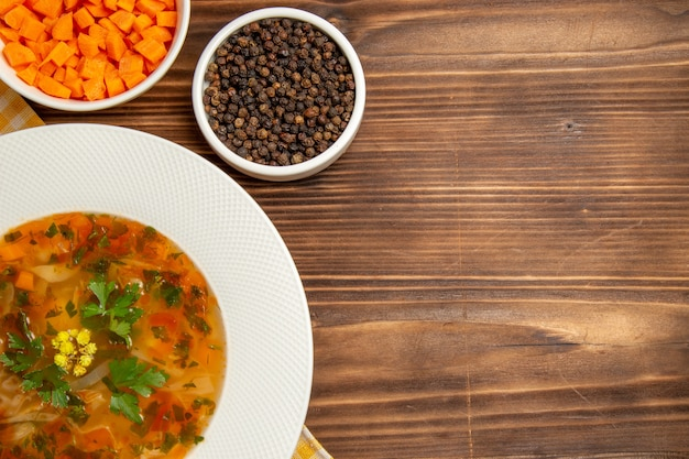 Vista superior saborosa sopa de vegetais com temperos em uma mesa de madeira marrom.
