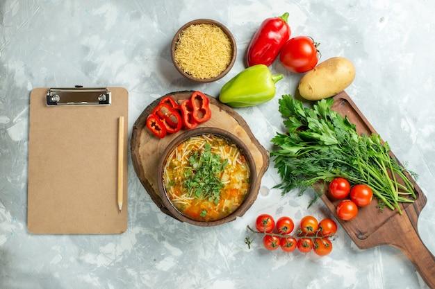 Vista superior saborosa sopa de vegetais com verduras e vegetais frescos em comida de sopa de refeição de vegetais de parede branca