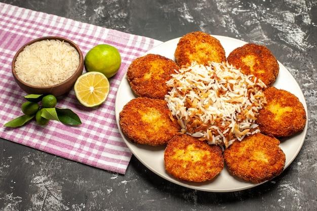 Vista superior saborosas costeletas fritas com arroz cozido em comida escura de rissole de mesa