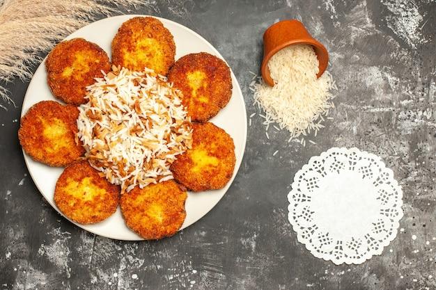 Vista superior saborosas costeletas fritas com arroz cozido em prato de superfície cinza foto de carne
