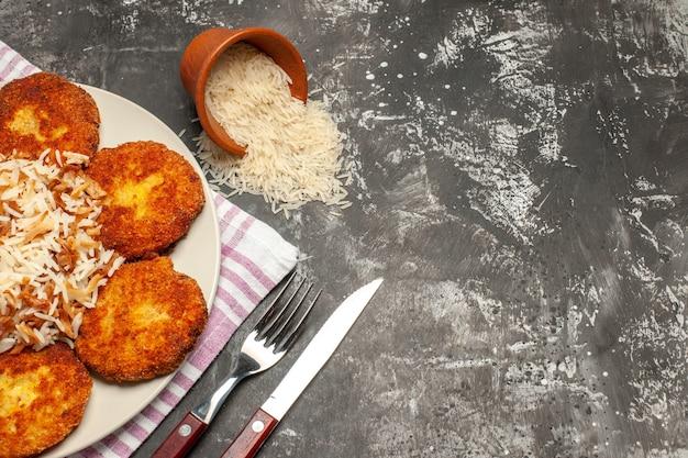 Vista superior saborosas costeletas fritas com arroz cozido em prato escuro de rissole de mesa