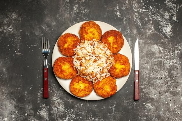 Vista superior saborosas costeletas fritas com arroz cozido na superfície escura foto prato refeição carne
