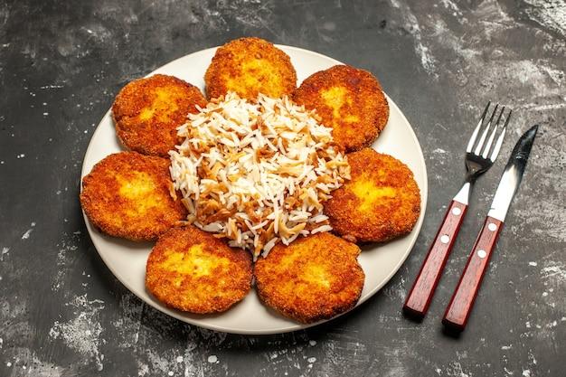 Vista superior saborosas costeletas fritas com arroz cozido na superfície escura prato de refeição
