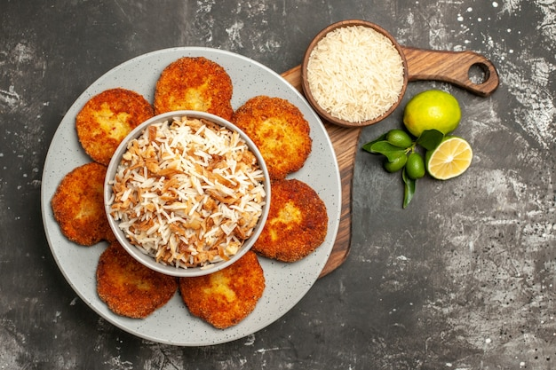 Vista superior saborosas costeletas fritas com arroz cozido no prato de rissole de carne de superfície escura