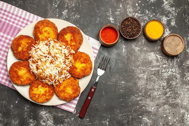 Vista superior saborosas costeletas fritas com arroz e temperos na superfície escura de rissole de carne