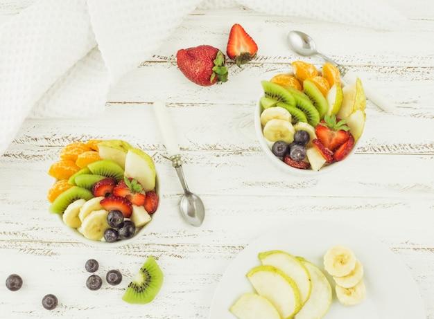 Vista superior saborosas saladas de frutas rodeadas de frutas