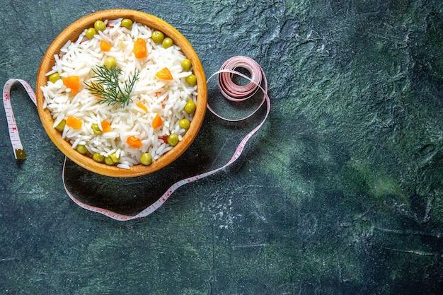 Vista superior saboroso arroz cozido com feijão dentro do prato na mesa escura