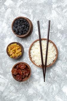 Vista superior saboroso arroz cozido dentro de um prato marrom com passas em branco claro