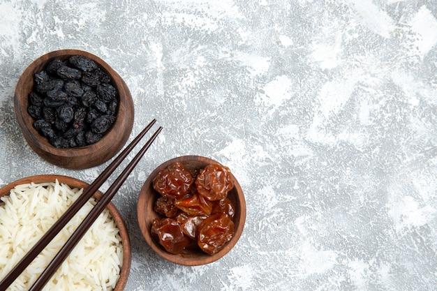 Vista superior saboroso arroz cozido dentro de um prato marrom com passas em uma mesa branca clara
