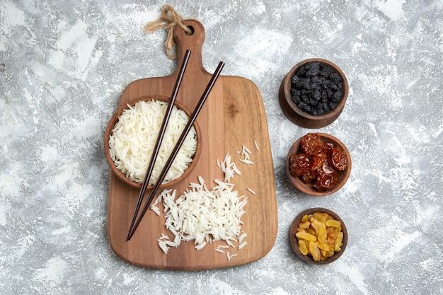 Vista superior saboroso arroz cozido dentro de um prato marrom com passas no branco