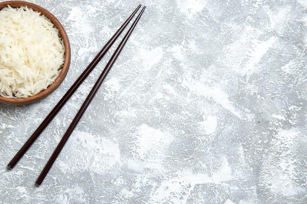 Vista superior saboroso arroz cozido dentro de um prato marrom em branco claro