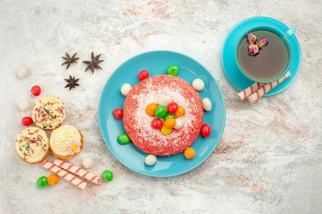 Vista superior saboroso bolo rosa com doces e uma xícara de chá na superfície branca.