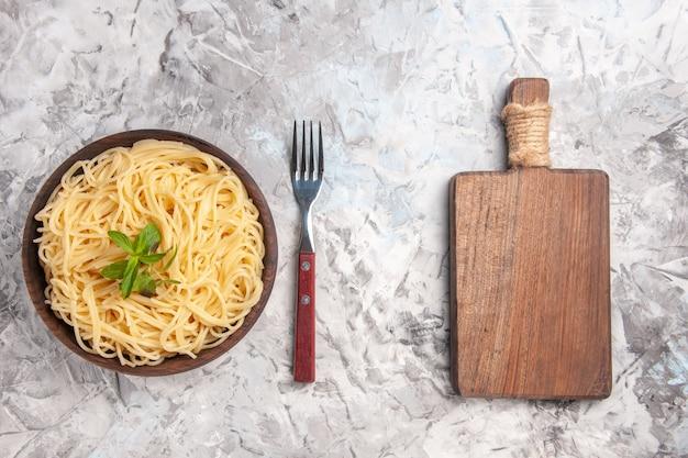 Vista superior saboroso espaguete com folha verde em massa de mesa branca prato de massa