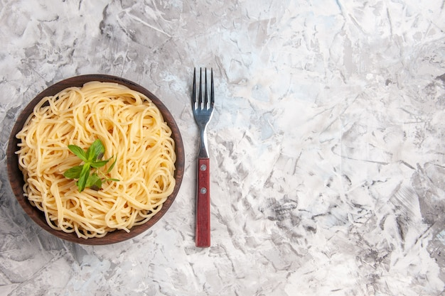 Vista superior saboroso espaguete com folha verde no prato de massa branca