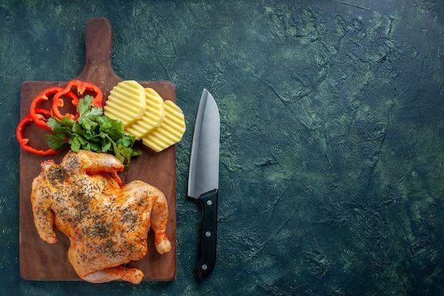 Vista superior saboroso frango cozido temperado com batatas e pimenta fatiada em fundo escuro cor de carne prato jantar churrasco