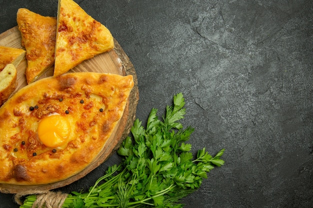 Vista superior saboroso pão com ovo cozido fatiado com verduras no fundo cinza pão pão massa comida café da manhã
