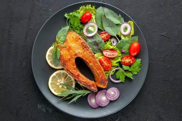 Vista superior saboroso peixe cozido com legumes e rodelas de limão na mesa escura