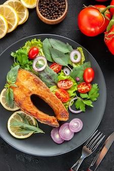 Vista superior saboroso peixe cozido com legumes frescos e rodelas de limão na mesa escura