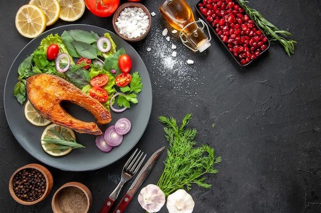 Vista superior saboroso peixe cozido com legumes frescos na mesa escura