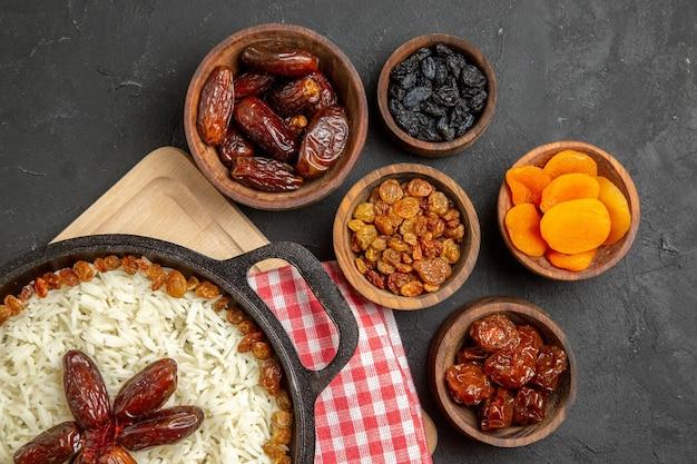 Vista superior saboroso prato de arroz cozido plov com passas diferentes no fundo escuro prato de passas comida arroz óleo jantar