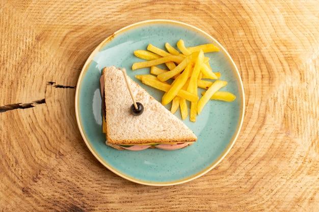 Vista superior saboroso sanduíche com presunto verde-oliva tomate vegetais dentro do prato com batatas fritas na foto de madeira de fundo