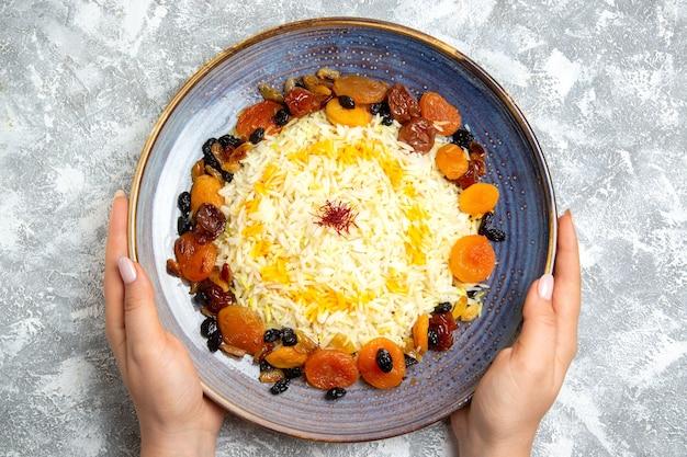 Vista superior saboroso shakh plov prato de arroz cozido com passas dentro do prato em branco claro