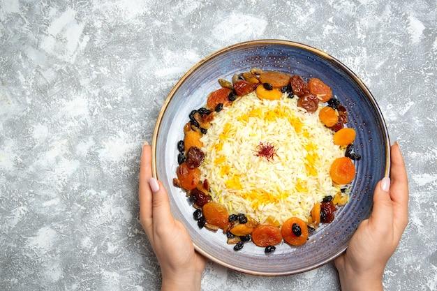 Vista superior saboroso shakh plov prato de arroz cozido com passas dentro do prato na mesa branca