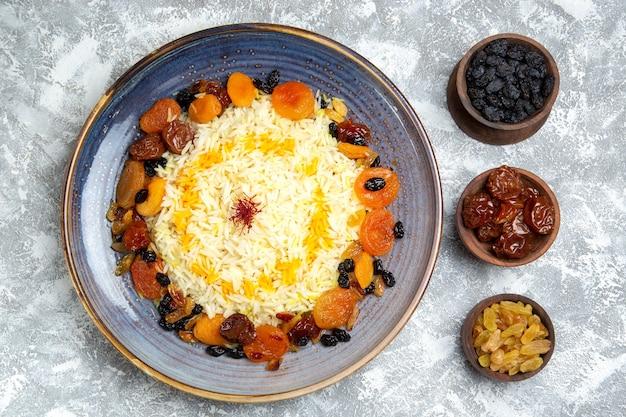 Vista superior saboroso shakh plov prato de arroz cozido com passas dentro do prato no chão branco