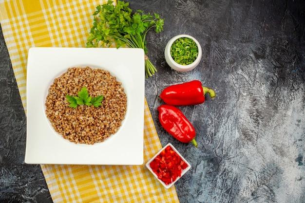 Vista superior saboroso trigo sarraceno cozido com verduras e pimentões na mesa cinza claro