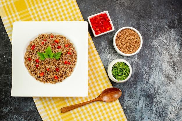 Vista superior saboroso trigo sarraceno cozido em prato branco com verduras em mesa cinza claro