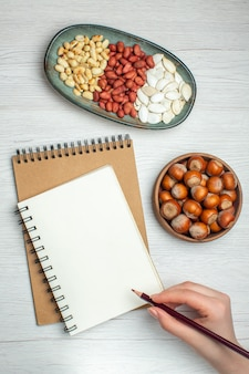 Vista superior saborosos amendoins frescos com sementes brancas e avelãs na mesa branca